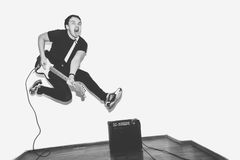 Awesome crazy fashion young musician rock guitar player jumps with passion in studio. Stylish rocky emotional man. Black Stock Photo