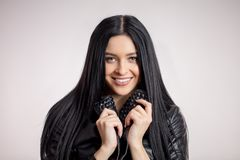 Awesome dark-haired model holding the collar of black leather jacket stock image