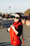 Awesome girl in fashionable round sunglasses, a red vest, a black t-shirt, jeans looking at the camera, smiling. Bright Stock Photos