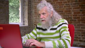 Awesome hairy aged caucasian man with long white beard is typing and demonstrating winning gesture with his fist while