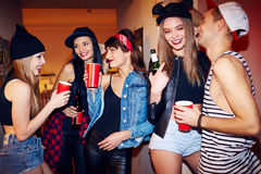 Awesome House Party. Cool students hanging out drinking beer and talking in corridor of big private house at swag party Stock Photo
