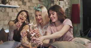 Awesome ladies in pajamas enjoying the time together in the bedroom playing with a sparkling fireworks , at sleepover. Night party stock footage