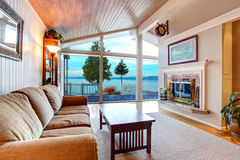 Awesome living room interior with sloped wooden ceiling and water view. Awesome living room interior with sloped wooden ceiling, floor to ceiling windows, and Stock Image