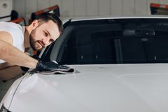 Awesome male employee using clean cloth aafter washing the car. Close up photo. copy space royalty free stock images