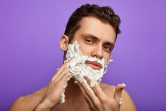 Awesome man using cream in the blue background stock photos