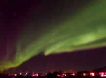Awesome Northern Lights Swirling over a Small Town in Iceland stock photos
