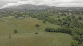 Awesome aerial view above oak forests and green valley with rural settlements between hills and village skyline in a dramatic over