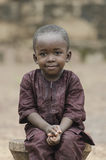 Awesome proud African boy sitting outdoors. Little african boy sitting on wooden bench and looking at camera with blurred background Royalty Free Stock Images