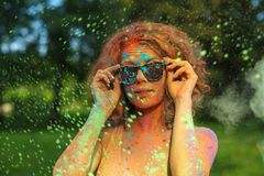 Awesome redhead model with curly hair having fun with colorful paint at the park. Concept for festival Holi. Awesome redhead woman with curly hair having fun stock photo