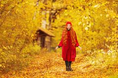 Awesome redhead woman with long curly hair in red coat on blurred autumn background. Girl on awesome background of forest. With orange autumn leaves. Leaves stock image