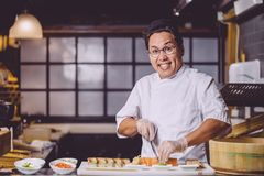Awesome smiling Chinese man using knife to cut sushi into pieces royalty free stock images