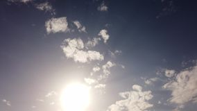 Awesome summer sky with sun and scenic altocumulus clouds flies in a blue sky with back lights effects. Awesome summer sky with sun and scenic altocumulus clouds stock footage