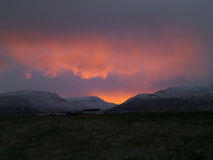 Awesome sunset sky over snow capped mountain range Stock Image