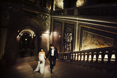 Awesome wedding couple goes upstairs in the dark theatre.  Stock Photo