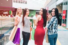 Awesome and well-dressed girls are standing and posing. They are looking backwards on camera, waving and smiling. They. Look happy stock photos