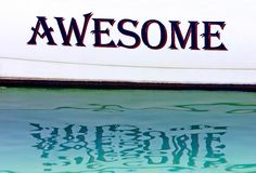 Awesome written on the side of a boat in Spain Stock Image