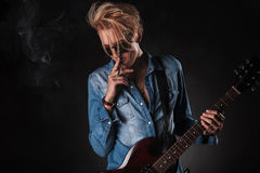 Awesome young guitarist smoking and playing Royalty Free Stock Photography