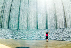 Awestruck woman at fountain. With arms raised Stock Photo