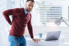 Upset man standing next to the table and touching his aching back. Awful feeling. Young bearded upset man feeling unwell while standing with his hand on a table Royalty Free Stock Photography