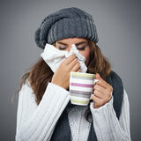 Awful flu. Young woman having flu and blowing her nose at handkerchief Stock Images