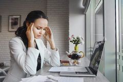 Awful headache makes woman suffer during working day. Stock Photo