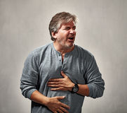 Awful man expression. Mature man with awful face expressions portrait over gray background stock image