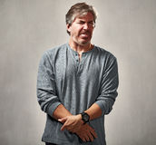 Awful man expression. Mature man with awful face expressions portrait over gray background royalty free stock image