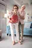 Expecting woman standing while having awful pain. Awful pain. Expecting women standing in the living room while having awful pain in the middle of her tummy royalty free stock photography