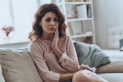 Awful toothache. Frustrated young woman suffering from toothache while sitting on the sofa at home stock images