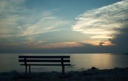 Ławka morzem przy zmierzchem Obrazy Stock