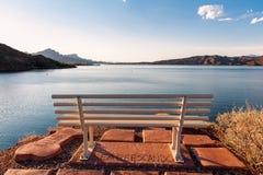 Ławka przed jeziorem pod niebieskim niebem Obrazy Royalty Free
