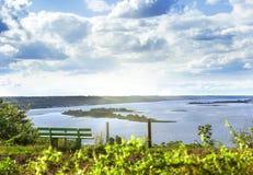 Ławka przed rzecznymi wyspami i cloudscape Fotografia Stock