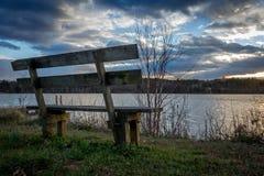 Ławka przegapia jezioro przy zmierzchem Zdjęcie Royalty Free