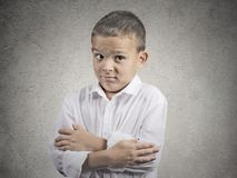Awkward situation. Portrait embarrassed child boy looking with misunderstanding at you camera, grey wall background. Human face expression emotion feeling body royalty free stock photo