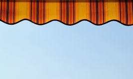 Awning detail. Detail of an awning shading a terrace over blue sky royalty free stock images
