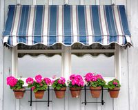 Awning with flowers. Blue and white awning with flowers in the front Royalty Free Stock Image