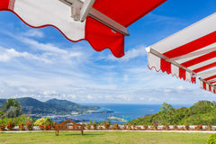 Awning over bright sunny blue sky with bench and sea view. Red and white Awning over bright sunny blue sky with bench and sea view stock image