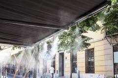 Awning sprinklers splashing water at terrace bar Stock Photos