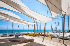 Awnings in sails shape covering relax area on beach. Awnings in sails shape covering relax area near sailing boats on the sandy beach in Calafell town, coast of Stock Photo