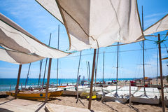 Awnings in sails shape covering relax area. Near sailing boats on sandy beach in Calafell town, coast of Mediterranean sea, Catalonia, Spain Stock Images