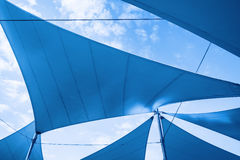 Awnings in sails shape over cloudy sky Stock Photography