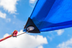 Awnings in sails shape over cloudy sky background. Detail of securing the tent from the sun to the cable Royalty Free Stock Photo