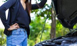 Awoman met een gebroken auto en zij opent bonnet stock fotografie