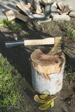 Ax chopping wood on chopping block Royalty Free Stock Photo