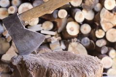 Ax cutting wood with unfocused logs in the background stock images