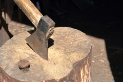 The ax is hammered into a wooden deck. Next is a hammered anvil for riveting a scythe royalty free stock image