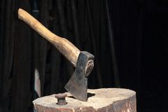 The ax is hammered into a wooden deck. Next is a hammered anvil for riveting a scythe royalty free stock photography