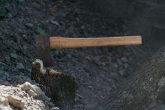 An ax hatchet stabbed in a stump royalty free stock image