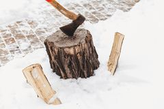Ax sticks out in stump against background of white snow stock photography