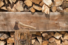 Ax stuck and cut wood. Ax stuck in a chopping block, stored behind the cut wood Stock Images